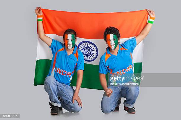 Male friends with face painted in a tricolor holding Indian flag over gray background