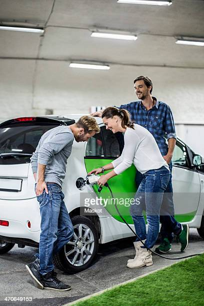 Male friends with woman charging electric car at gas station