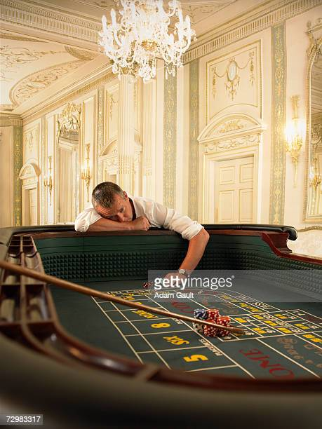 male gambler losing at craps table in casino - gambling table stock pictures, royalty-free photos & images