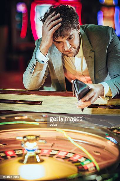 Male gambler losing at electronic roulette in  casino