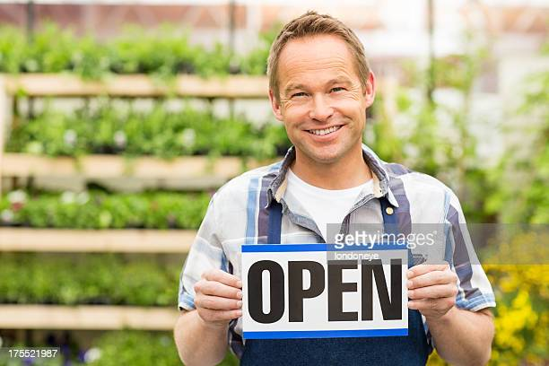 Male Garden Worker Holding an Open Signboard