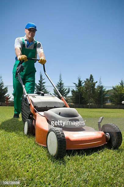 Male Gardener in Overalls Pushing Lawn Mower