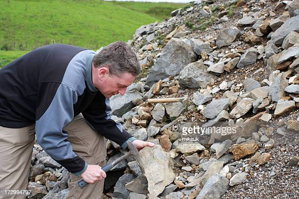male Geologist scientist with hammer examining rocks
