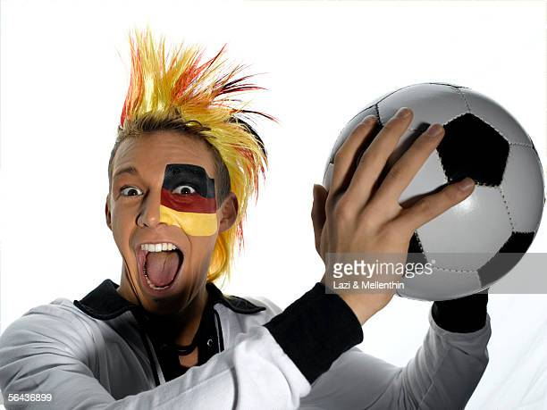 Man with German flag painted on face, holding soccer ball, portrait