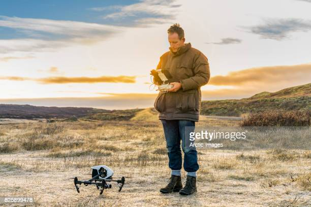 Male getting ready to fly a drone by a glacier, Iceland