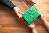 Male gives a gift present to female with wooden copy space background.happiness moment