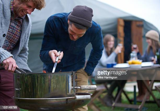 Male Glampers cooking food on barbecue.