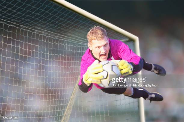 male goalie catching ball in midair - making a save sports stock pictures, royalty-free photos & images