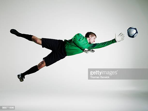 male goalie diving in mid air to stop soccer ball - goalie goalkeeper football soccer keeper stock pictures, royalty-free photos & images