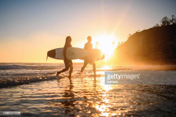 male gold coast surfers coming out of water at dawn - gold coast queensland stock pictures, royalty-free photos & images