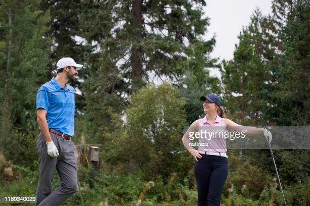 male golf coach teaches the young woman to play golf - teeing off stock pictures, royalty-free photos & images