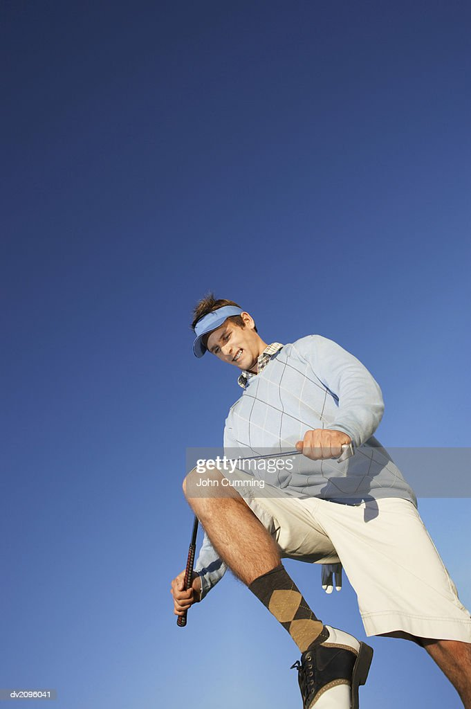 Male Golf Player Breaking a Golf Club With His Knee : Stock Photo