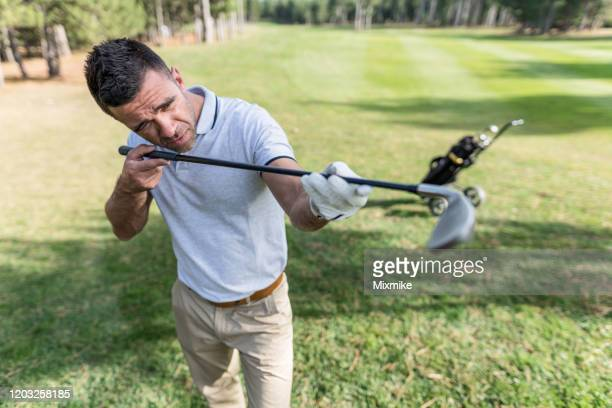 male golf player examining the golf equipment - tee sports equipment stock pictures, royalty-free photos & images