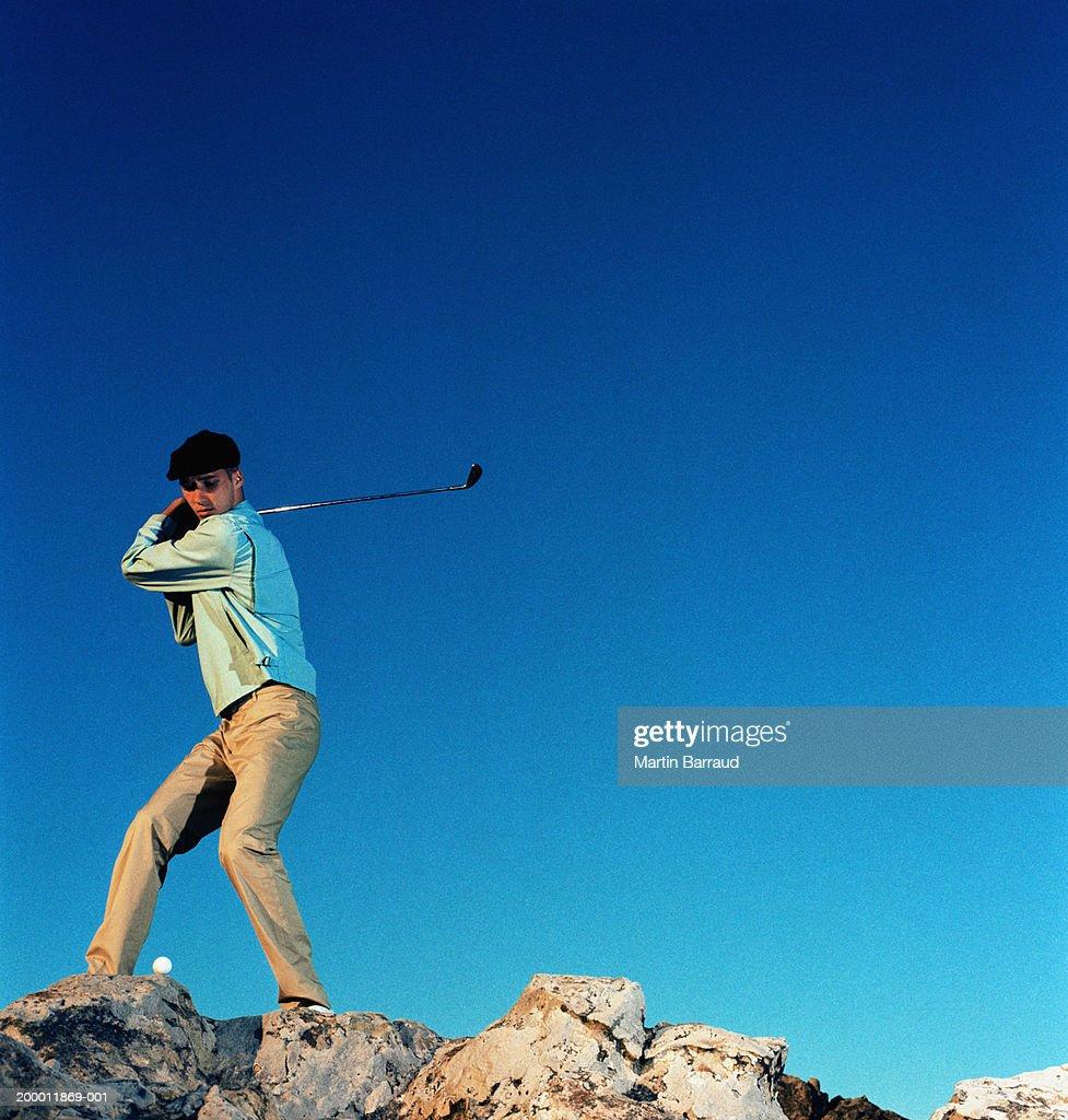 Male golfer driving ball off rocks : Stock Photo