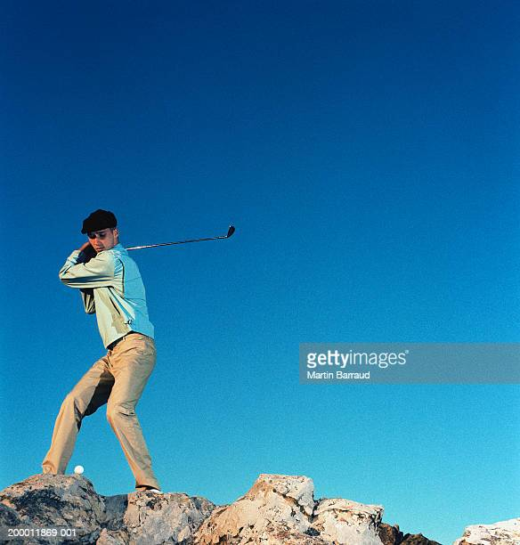 Male golfer driving ball off rocks