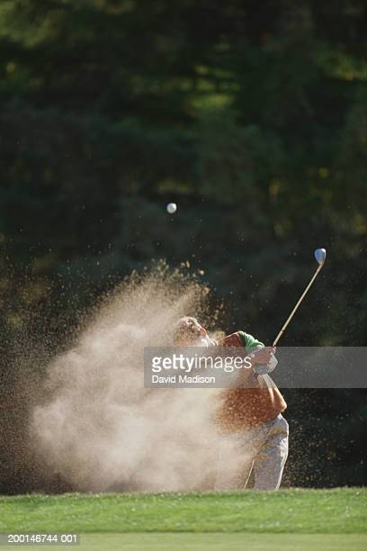 male golfer hitting out of a sand trap onto the green - bunker stock pictures, royalty-free photos & images