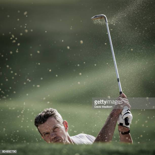 Male golfer hitting out of sand trap