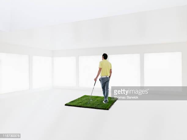 Male golfer holding club on grass in home