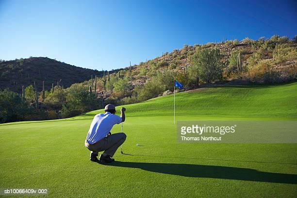 male golfer lining up putt on golf course - putting - fotografias e filmes do acervo