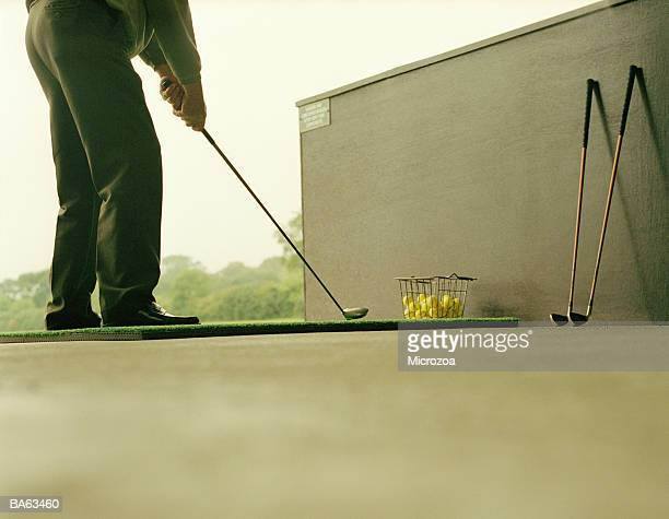 male golfer lining up stroke on practice range, low section - microzoa stock pictures, royalty-free photos & images