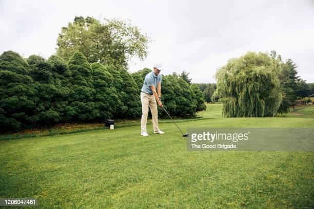 male golfer preparing to hit tee shot - ティーグラウンド ストックフォトと画像