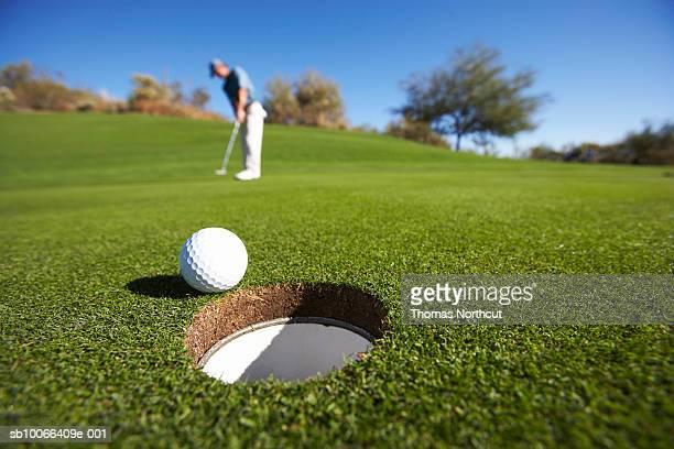 male golfer putting on golf course - golfe imagens e fotografias de stock