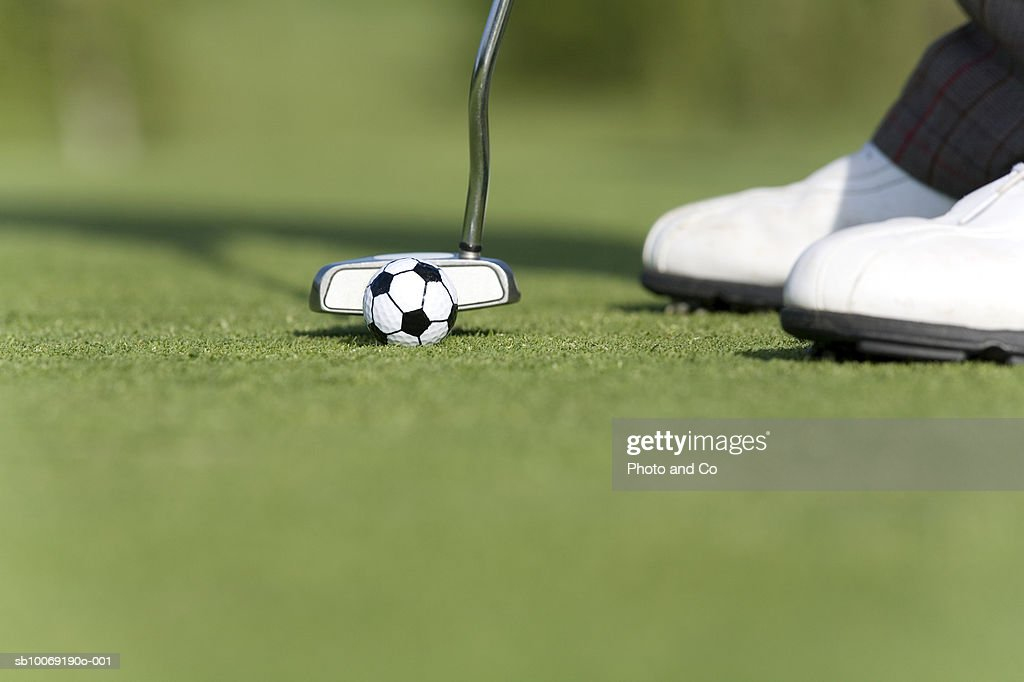 Male golfer putting soccer golf ball on green, low section, close up : Stockfoto