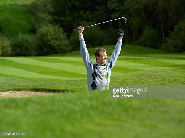 male golfer standing in bunker holding golf club, arms raised, smiling - bunker stock pictures, royalty-free photos & images