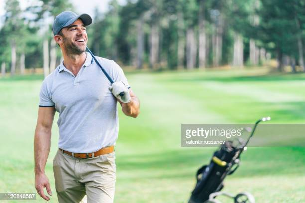 male golfer standing on golf course - golfer stock pictures, royalty-free photos & images