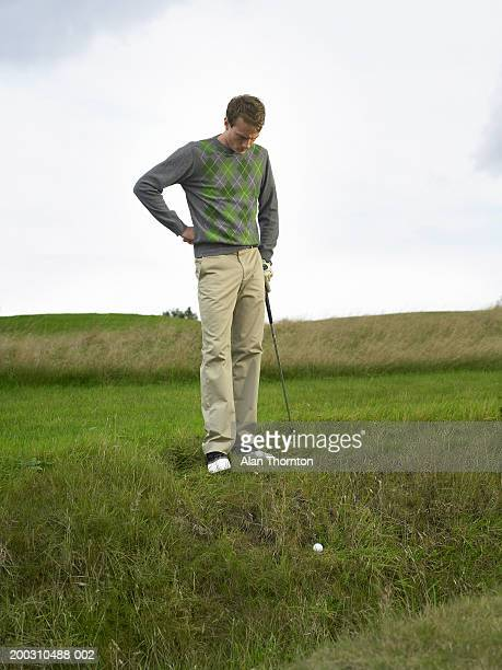 male golfer standing with hand on hip, looking at ball by ditch - 埋まる ストックフォトと画像