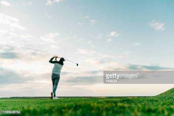 male golfer swinging club at course during sunset - golf stock pictures, royalty-free photos & images