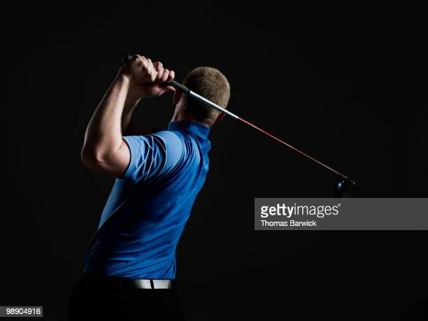 Male golfer swinging club rear view