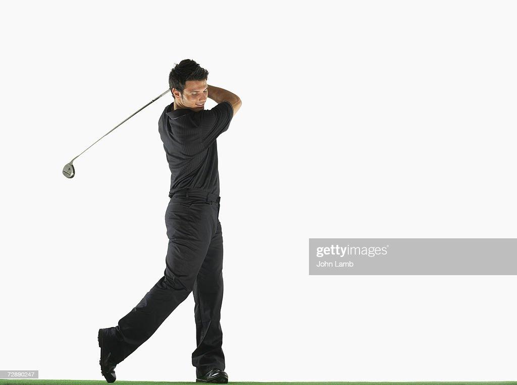 Male golfer swinging golf club : Stock Photo