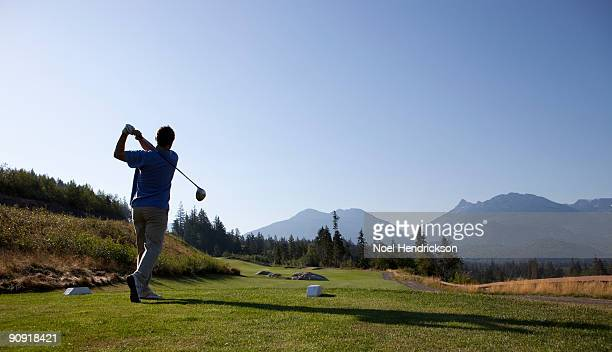 male golfer swinging with driver