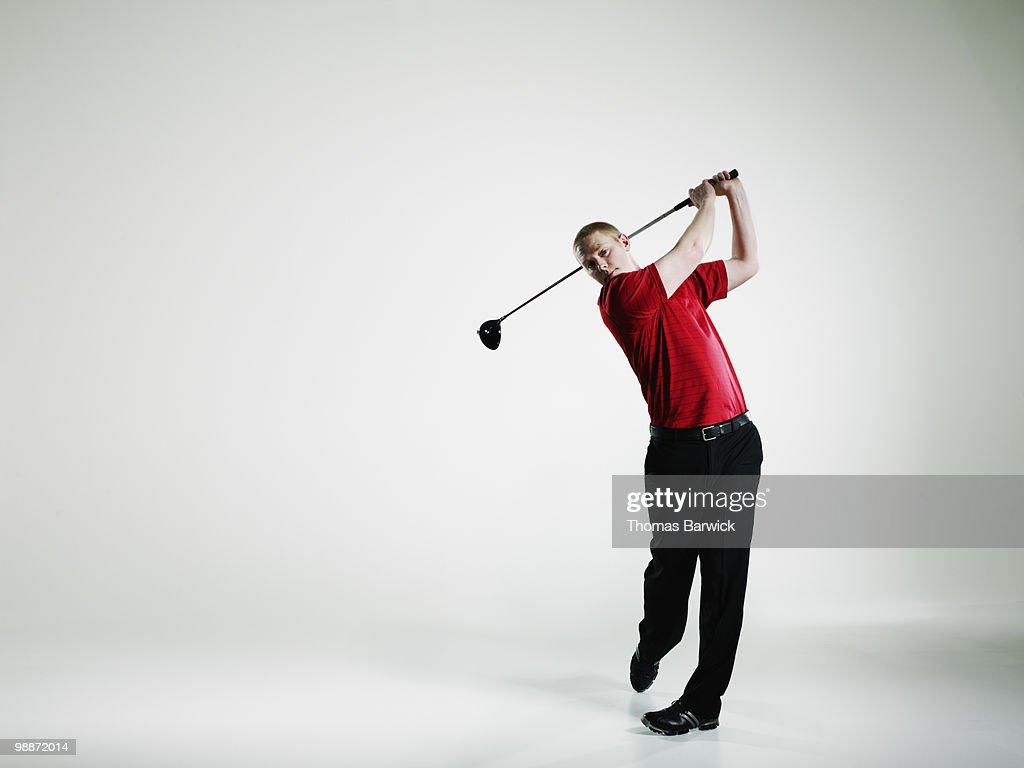 Male golfer teeing off with driver golf club : Stock Photo