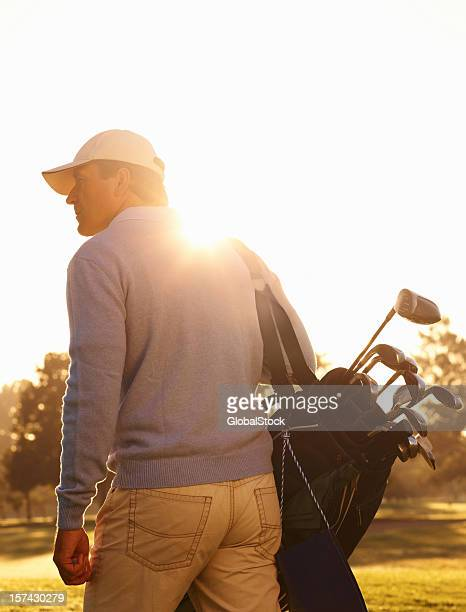 Male golfer with his golf kit at play