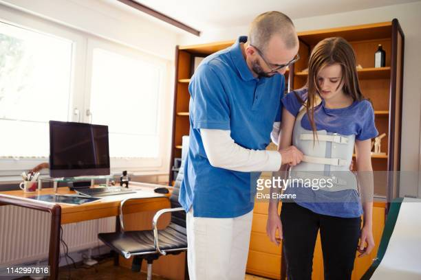 male gp in a german medical office, assessing teenage girl wearing back brace for scoliosis correction - brace stock pictures, royalty-free photos & images