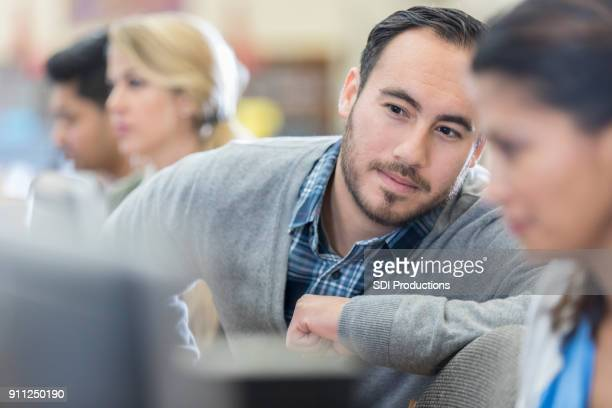 Male graduate student helps classmate in computer lab