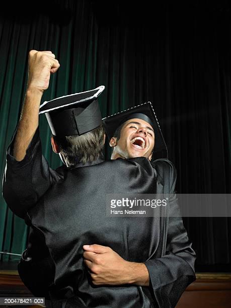 male graduates hugging, one raising fist in celebration - hans neleman ストックフォトと画像