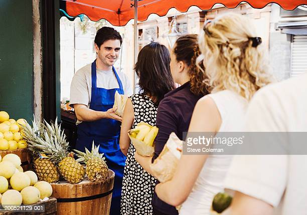 Male greengrocer serving queue of customers at market