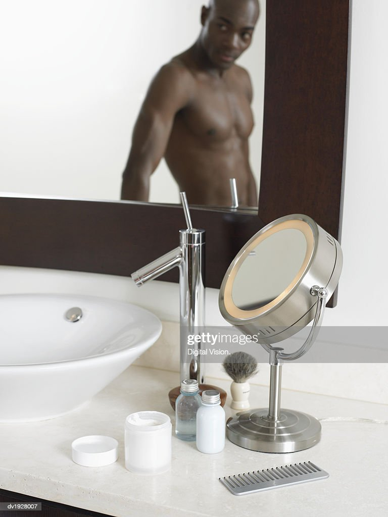 Male Grooming Accessories in a Bathroom, Man Looking at His reflection in a Mirror : Stock Photo