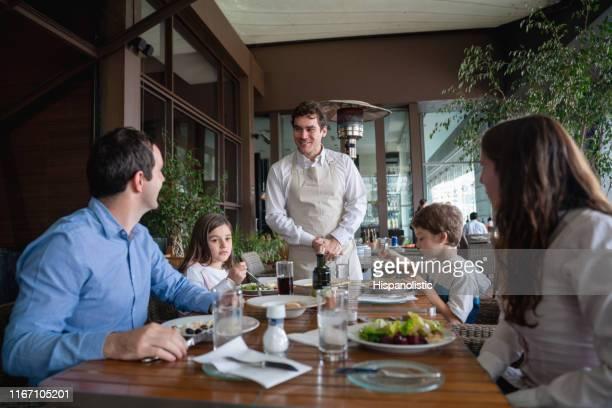 männliche gäste mit seiner familie genießen eine mahlzeit im hotelrestaurant und bestellen etwas an freundlichen kellner - gast stock-fotos und bilder