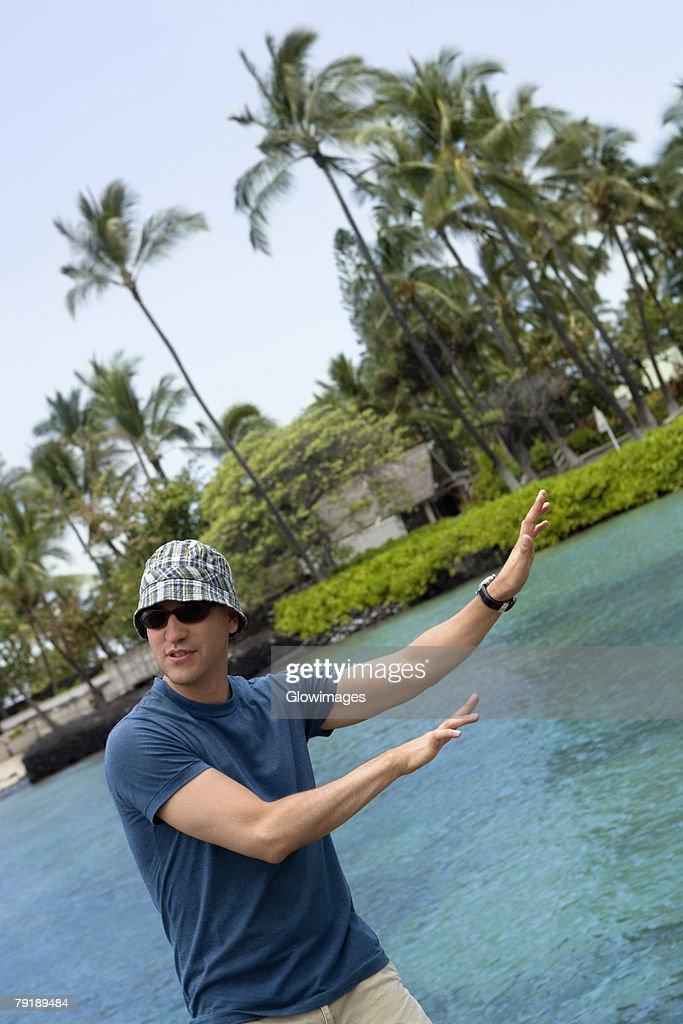 Male guide beckoning towards the sea, Captain Cook's Monument, Kealakekua Bay, Kona Coast, Big Island, Hawaii islands, USA : Stock Photo