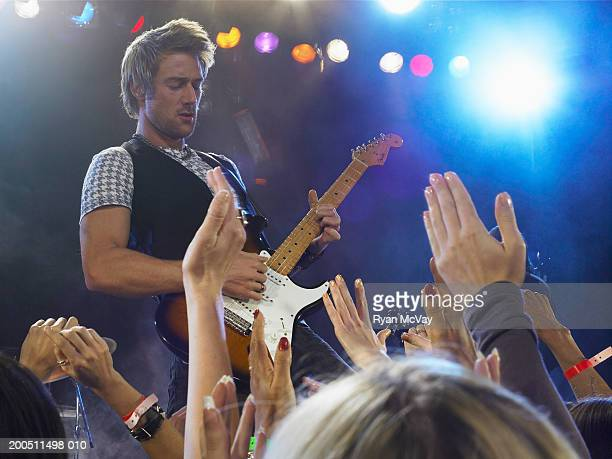 Male guitarist performing on stage, view from audience