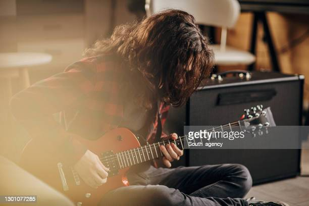 male guitarist playing electric guitar on the floor at home - rock music stock pictures, royalty-free photos & images
