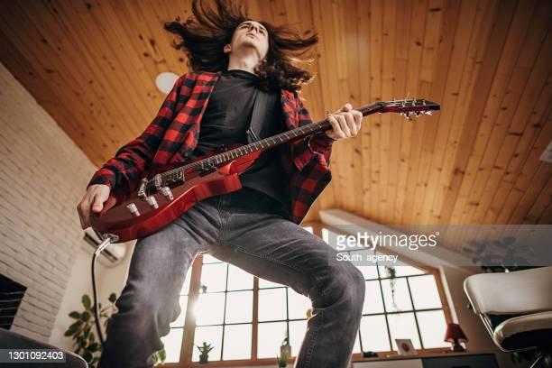 chitarrista maschile che suona la chitarra elettrica mentre salta - chitarrista foto e immagini stock