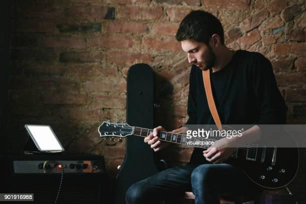 Mannelijke gitarist gitaarspelen met Tablet op versterker