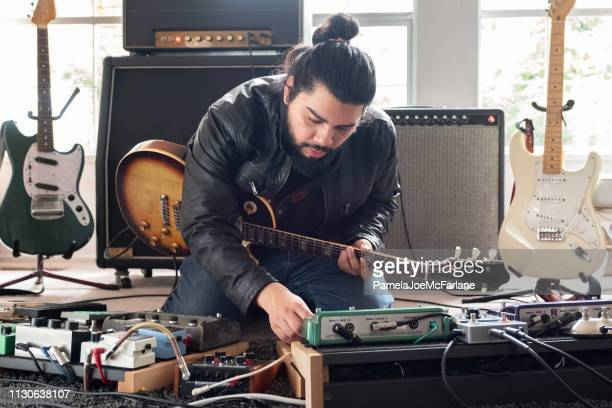 male guitarist surrounded by sound equipment adjusting sound effects pedals - amplifier stock pictures, royalty-free photos & images
