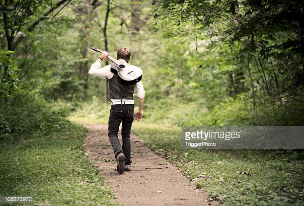 a male guitarist walking on a path - guitarist stock pictures, royalty-free photos & images