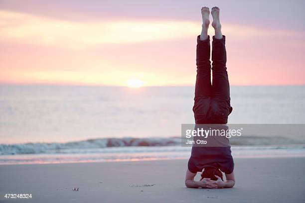 Male guy doing headstand at the beach of St.Peter-Ording, Germany